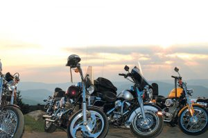 Motorcylces parked before a sunset